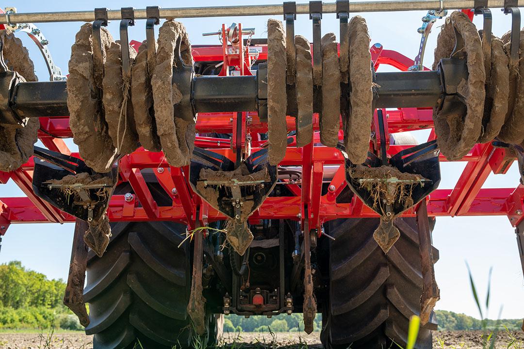Dit maakt de werking duidelijk. De cultivatortanden op 75 cm maken de grond los waar de maisplanten moeten wortelen. Daartussen beroert de machine de grond minder voor behoud van de structuur. De woelers die volgen, verplaatsen oppervlakkig wat grond van tussen de rijen naar de rij zelf, waardoor daar de ruwe, losse rug ontstaat. De parabolische rol achterop drukt de losse grond wat aan.