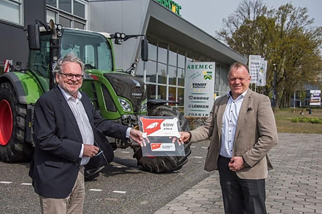 van Ravestein, algemeen directeur van de RDW, reikt de eerste erkenningssticker uit aan directeur Hans Quint van Abemec.